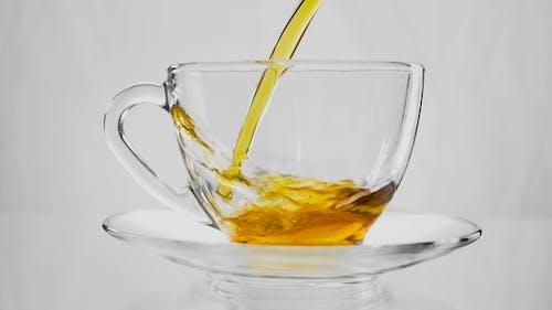 Green Tea. Pouring Tea Into a Glass Cup