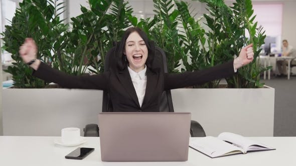 Business Woman See Good News on the Laptop, Laughs and Rejoicing in Success
