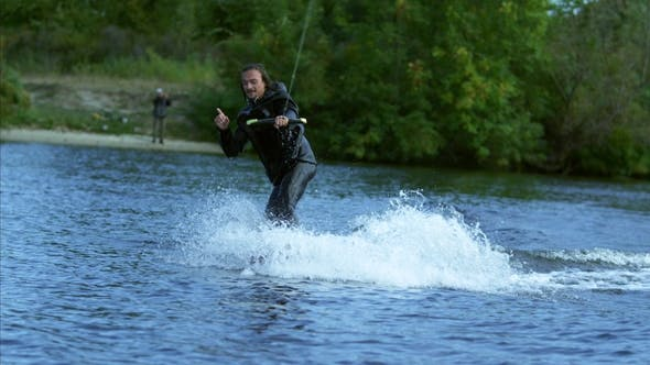 Thumbnail for Happy Man Wakeskier Making Signs By Hands During Movement on Lake Behind Boat