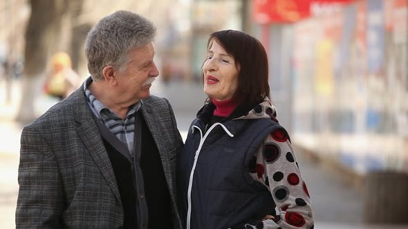 Cover Image for A Cheery Senior Couple Embraces Each Other and Talks on a City Street in Spring