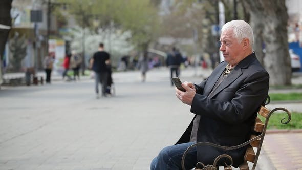 Thumbnail for A Grey-headed Man Browsing the Net on His Mobile in a City Street in Spring