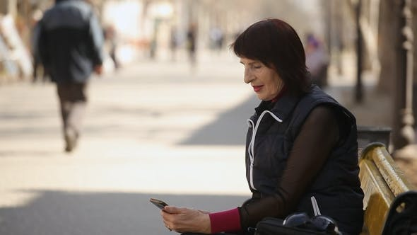 Thumbnail for A Middle-aged Woman Logs on the Net in Her Mobile and Sits on a Bench in Spring