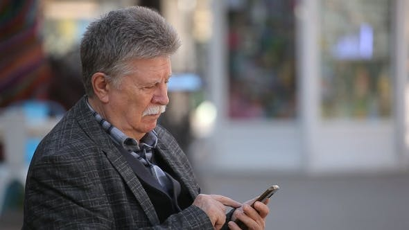 Cover Image for A Smart Old Man Logs on the Web on His Mobile in a City Street in Spring