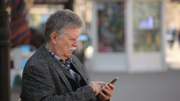 Thumbnail for A Wise Old Man Touches the Screen on His Mobile in a City Street in Spring