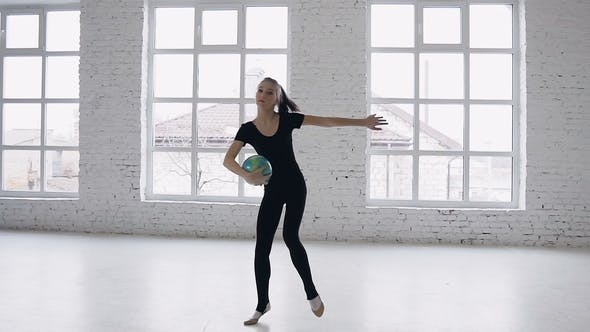 Thumbnail for Cute Teenage Gymnast Makes Training with Ball on a White Background Near Big Windows at Gymnastics