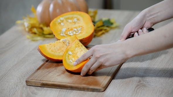 Thumbnail for Woman Cleaning Pumpkin on Wooden Kitchen Table. Male Preparing To Cutting Orange Pumpkin Piece.