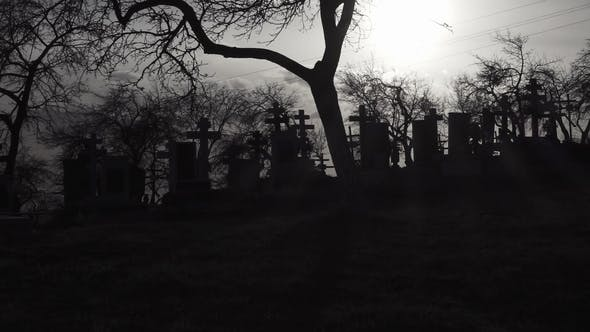 Cover Image for Old Graveyard with Ancient Crosses at Sunset. Scary Cemetery