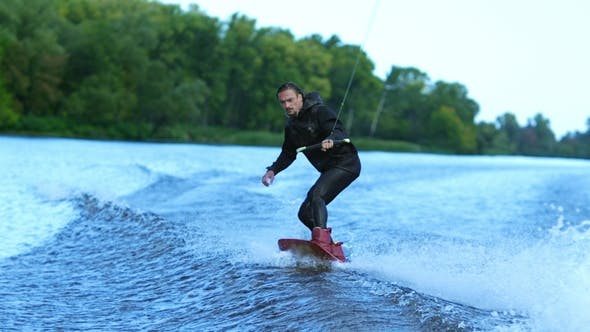 Thumbnail for Wakeboarder Waterskiing on River Behind Boat. Wake Boarding Rider