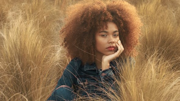 Thumbnail for Black Mixed Race Woman with Big Afro Curly Hair in Lawn Field with High Dry Autumn Hay Grass and