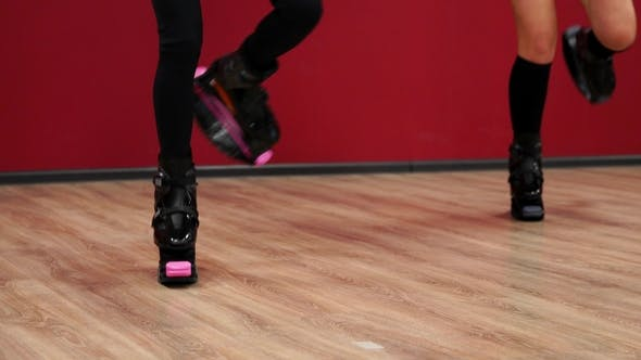 Cover Image for Beautiful Sexy Girls on a Red Wall Background Perform Fitness Exercises on Shoes with Spring