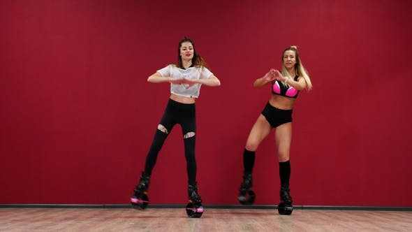 Thumbnail for Beautiful Sexy Girls on a Red Wall Background Doing Fitness Exercises in Special Shoes