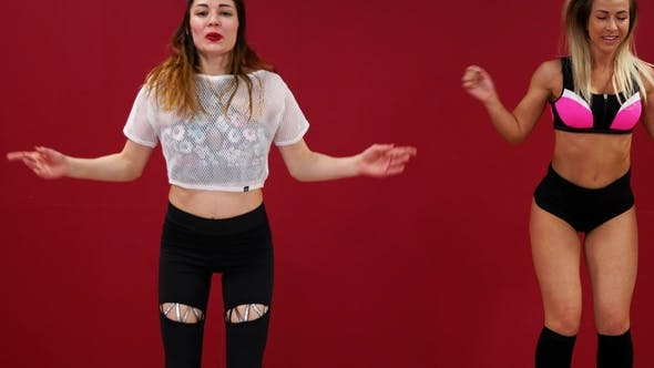 Thumbnail for Beautiful Sexy Girls on a Red Wall Background Perform Fitness Exercises on Shoes with Spring