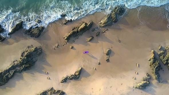 Thumbnail for Foamy Waves Roll on Beach with Girl Figure Aerial View