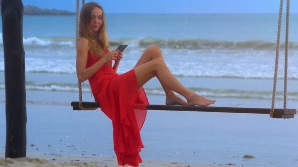 Thumbnail for Girl Swings on Seesaw Holding Smartphone against Tourist
