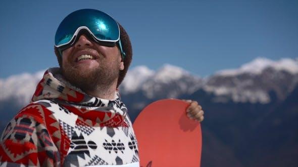 Thumbnail for Porträt eines fröhlichen Snowboarder in den Bergen