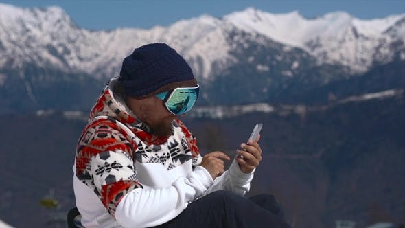 Thumbnail for Snowboarder Using Mobile Phone in the Mountains