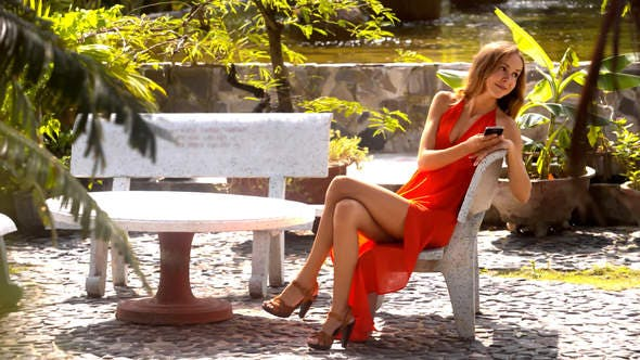 Thumbnail for Long Legged Girl Sits with Phone in Pictorial Park