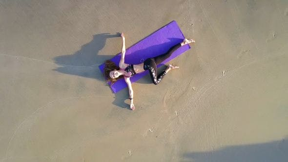 Thumbnail for Woman in Yoga Position on Ocean Beach Aerial View
