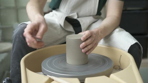 Thumbnail for Man in Apron on Potter's Wheel is Treating Product with Metal Tool