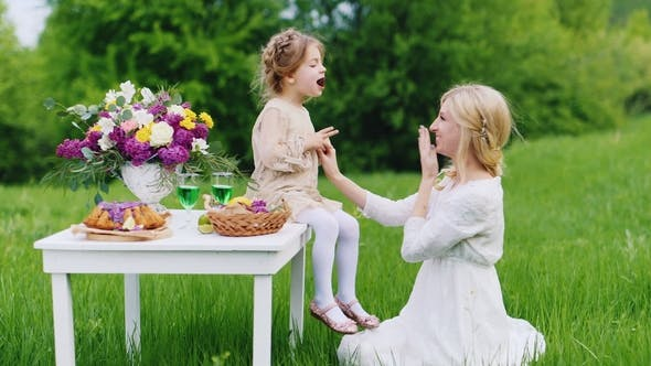 Cover Image for A Young Family Is Having Fun in Nature, Eating Sweets and Having Fun. St. Patrick's Day Picnic