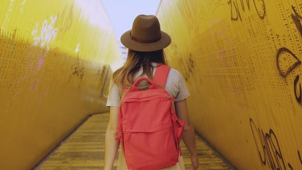 Thumbnail for Girl in Hat with Red Backpack Walks in Yellow Tunnel. Woman Walking Between Art Installation Bridge