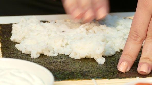 Chef Hands Kneading Rice on Nori Sheet