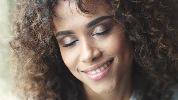 Cover Image for Portrait of a Curly Girl. Beautiful Make-up and Hairstyle. Headshot Portrait of a Attractive