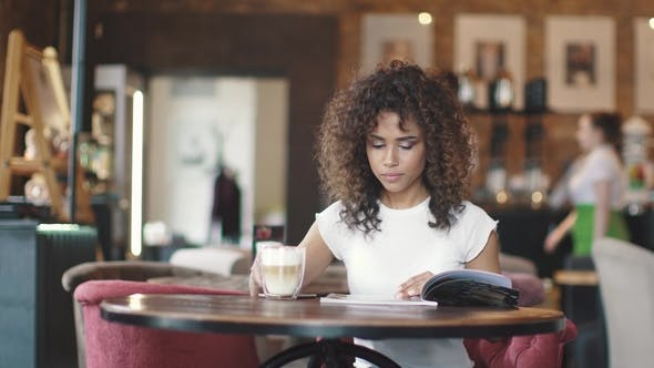 Thumbnail for the Girl Looks at the Menu in the Coffee House and Drinks Coffee with Milk. Young Woman Sitting at a