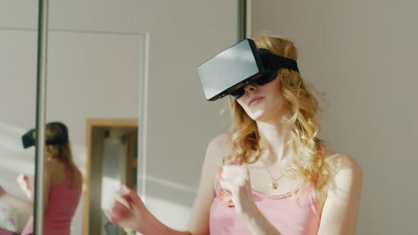 Cover Image for Young Woman Dancing at Home in a Virtual Reality Helmet