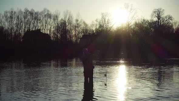 Thumbnail for Silhouetted Fisherman Standing in the Middle of Scenic River