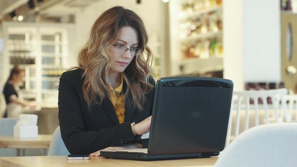 Young Woman in Business Suit Working on Laptop Sitting in Cafe. Informal Working Environment