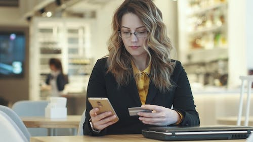 a Girl in a Business Suit Commits a Payment with a Credit Card Using a Smartphone