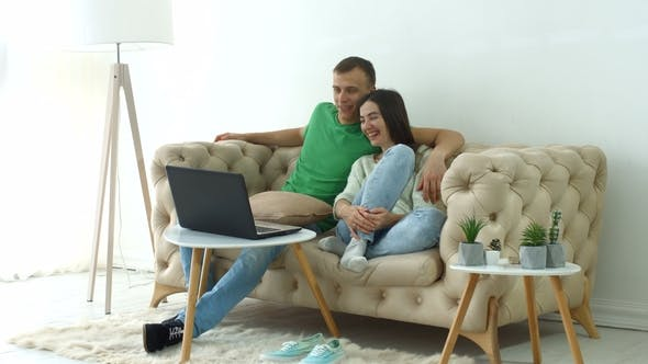 Thumbnail for Cheerful Couple Streaming Video Online on Laptop