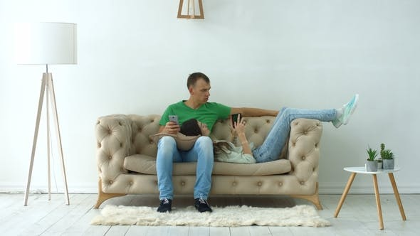 Thumbnail for Couple with Digital Devices Relaxing on the Couch