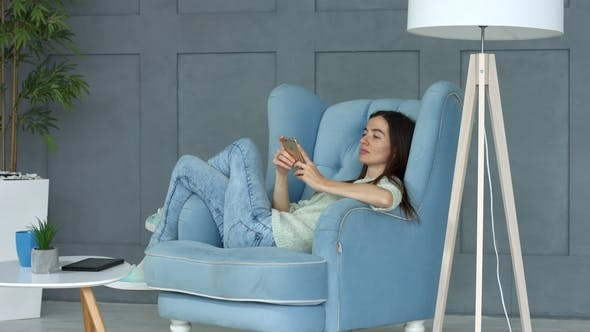Thumbnail for Relaxed Woman Browsing Social Media on Smart Phone