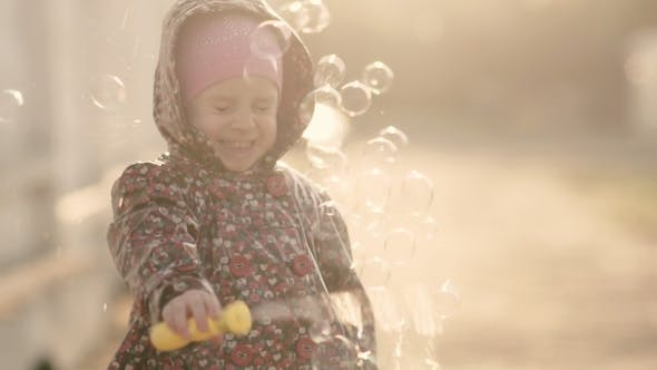 Thumbnail for Little Girl Blows Soap Bubbles at Sunset