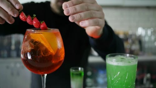 Guy Barkeeper Inserts Black Straws in Glass with Alcoholic Drink with Ice and Fresh Berries