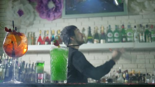 Vivid Alcoholic Drink with Fresh Strawberries Stand on Bar Table and Barkeeper on Background