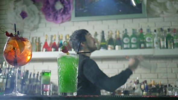 Thumbnail for Vivid Alcoholic Drink with Fresh Strawberries Stand on Bar Table and Barkeeper on Background