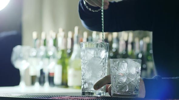 Thumbnail for Bar Spoon in Hands of Barman Stir Ice in Glass on Bar Counter on Background of Bottles