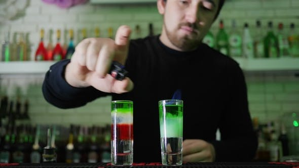 Cover Image for Barman with Lighter Sets on Fire Cocktail with Color Layers in Thin Glass on Bar