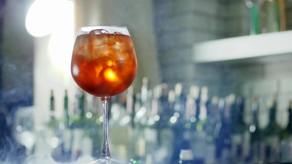 Cover Image for Vivid Cooling Cocktail with Ice Cubes in Large Wineglass  in Smoke at Bar