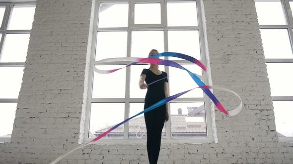 Thumbnail for Flexible Gymnast Dressed in Black Body with Colored Tape in Her Hand