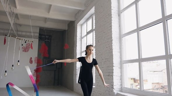 Thumbnail for Attractive Teenage Girl Gymnast Dancing with Colored Ribbon in Sport Gym in White Background Near