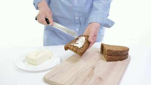 of Female Hands Spreading Butter on Bread in Kitchen. White Backgound