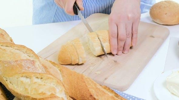 Thumbnail for Frische Brotscheibe und Schneidmesser auf rustikalem Tisch. Mit Wooman Händen