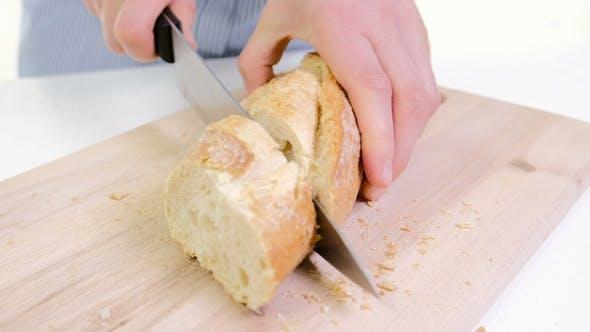 Thumbnail for Frau Hände Schneiden Brot in der Küche. Weibliche Hände Halten Messer, Schneiden Weiß Baguette