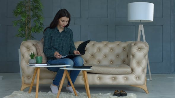 Thumbnail for Concentrated Woman Calculating Bills at Home