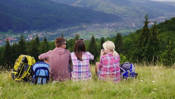 Cover Image for Friends of Tourists Sit in a Picturesque Place in the Background of the Mountains. They Rest, Admire