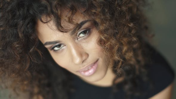 Thumbnail for Portrait of a Cute Young Woman with Curly Hair and a Charming Smile